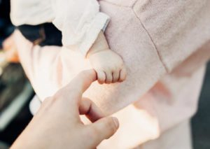 baby holds mum's finger
